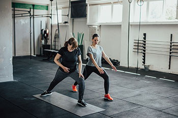 Woman doing yoga with trainer