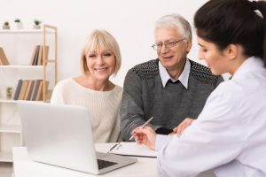elderly couple consulting with a female doctor at a desk
