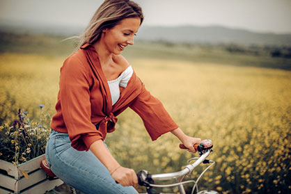 Young woman riding a bike through a field of flowers