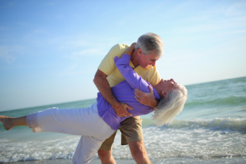 Senior couple dancing on a beach with ocean in background